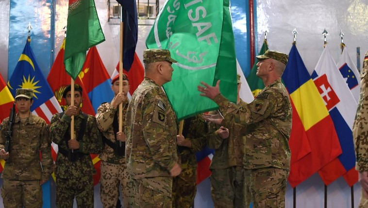 US General John Campbell (4L) lowers the flag of the NATO-led International Security Assistance Force (ISAF) during a ceremony marking the end of ISAF's