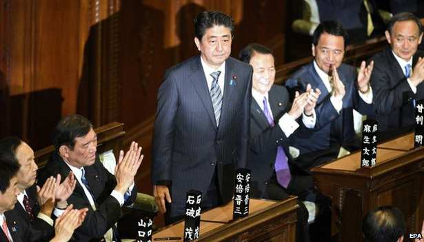 Japan's ruling Liberal Democratic Party (LDP) leader Shinzo Abe (C) receives applause from parliament members after he was re-elected as prime minister by the lower house of parliament in Tokyo on December 24, 2014.