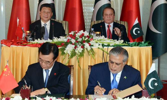 Xi Jinping, Nawaz Sharif look on as Pakistani Finance Minister Ishaq Dar and a Chinese official sign an MoU at PM House in Islamabad. — APP