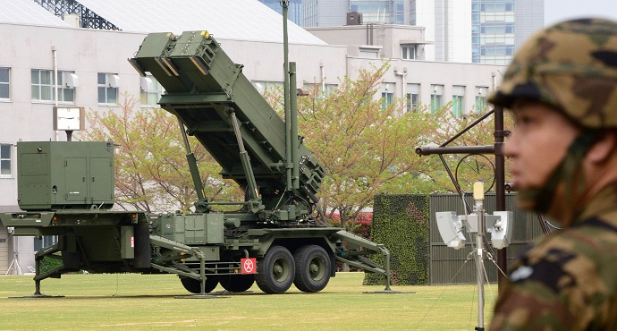 A Japanese soldier walks past a Patriot Advanced Capability-3 (PAC-3) missile launcher deployed at the Defence Ministry in Tokyo.
