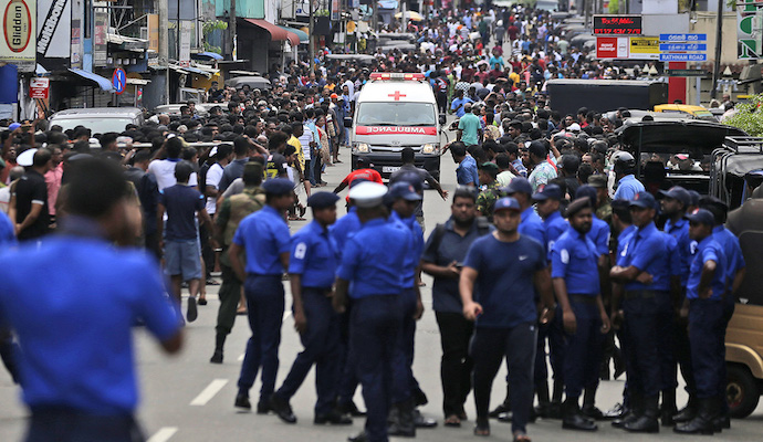 Sri Lankan police officers clear the road as an ambulance drives through carrying people injured in the blasts in Colombo. Photo courtesy: Eranga Jayawardena/AP Photo
