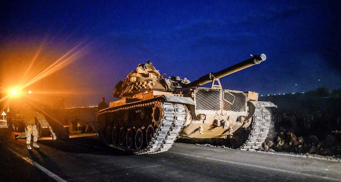 A Turkish tank drives towards the border with Syria [Bulent Kilic/AFP]