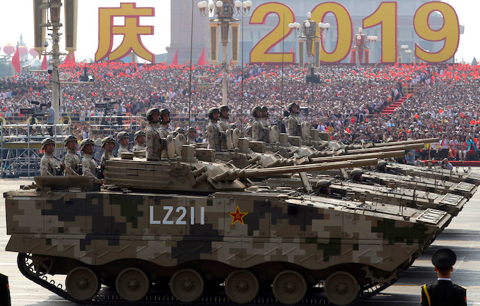 Military vehicles roll down as members of a Chinese military honour guard march. Credit: AP